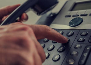 hand pressing numbers on an office phone