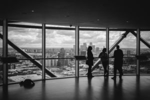 3 people discussing something in a building overlooking the city