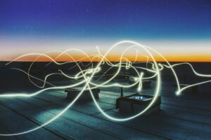 dark night scene with light on the horizon and glowing rope throughout the air that makes loops