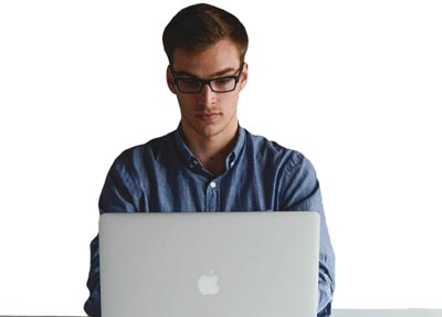 man in glasses working on a laptop computer